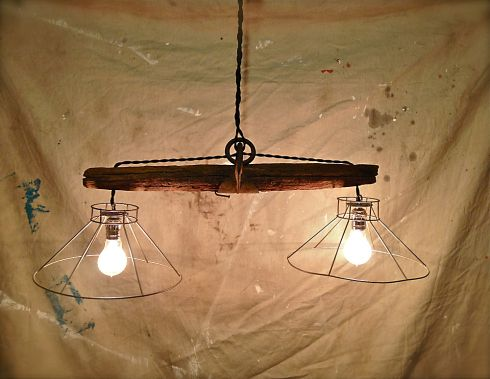 Rustic hanging light fixture made from and old plowing yoke