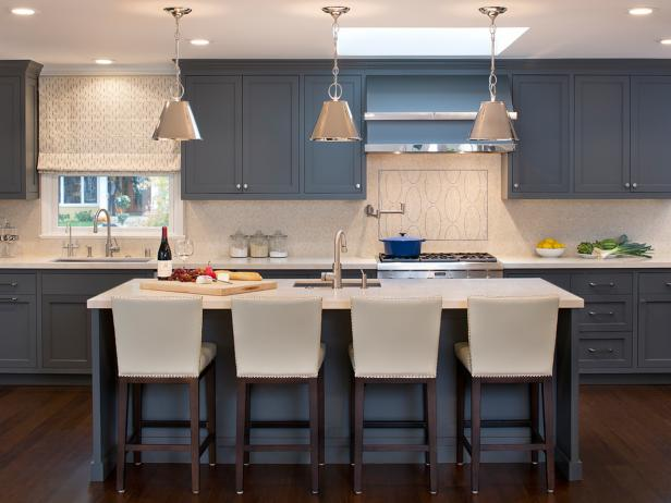 Transitional Kitchen With Blue Cabinets and White Barstools