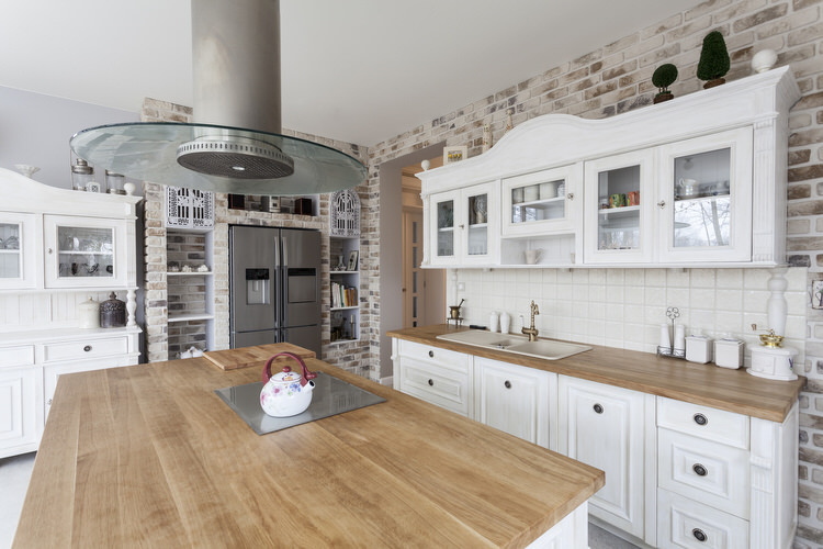 Solid surface countertops and modular Swedish cabinets freshen the look of  this European farmhouse. Task lighting is provided by metal industrial  pendants.