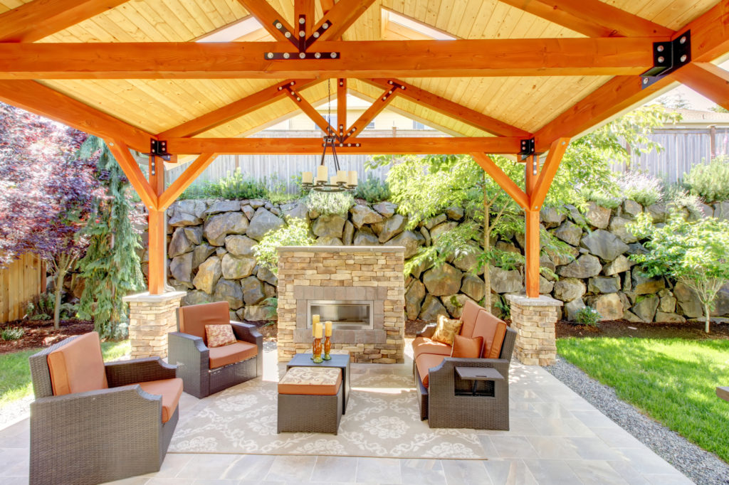 covered patio with fireplace, patio furniture, and lighting