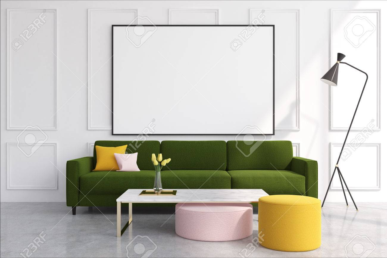 Stock Photo - White living room interior with a dark green sofa, colored  cushions lying on it and a horizontal poster hanging above it.