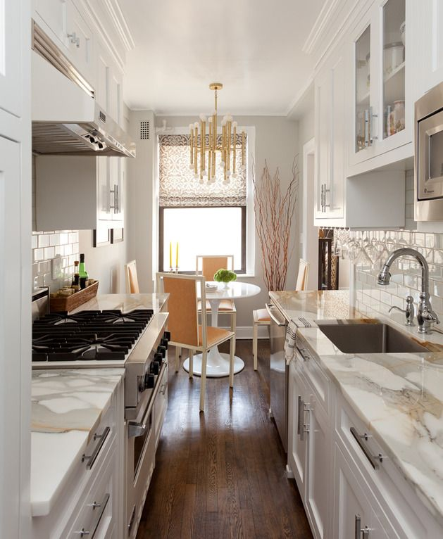 Small galley kitchen in NY apartment done very well. Saarinen Dining Table,  Jonathan Adler brass chandelier, marble counters, 3x6 subway tile with