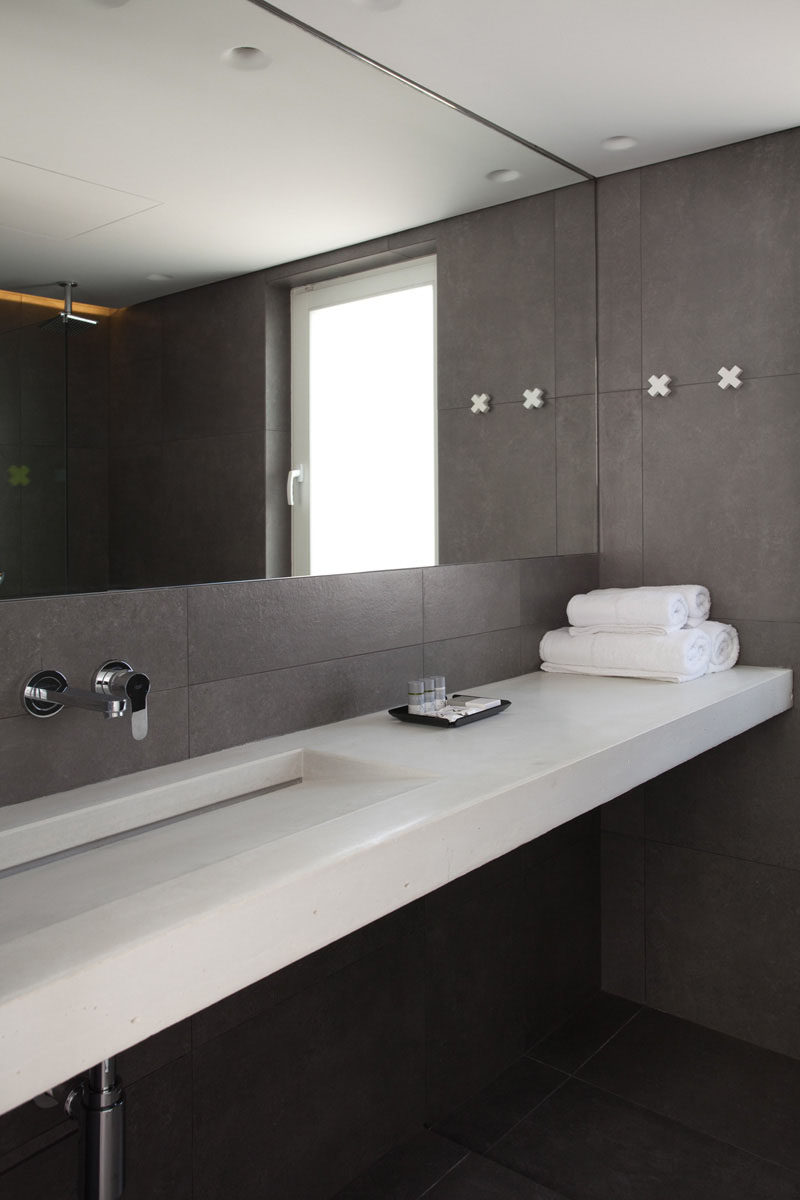 The mirror takes up most of the wall above the sink and makes the gray  bathroom feel larger and more open.
