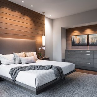 Large minimalist master dark wood floor and brown floor bedroom photo in  Other with beige walls