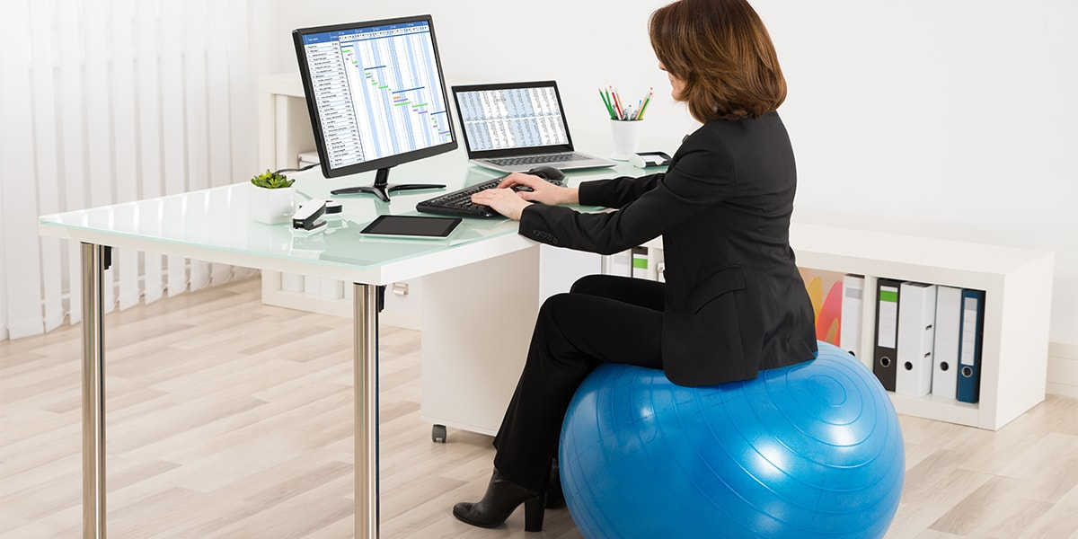 Businesswoman Sitting On Ball chair Working In Office