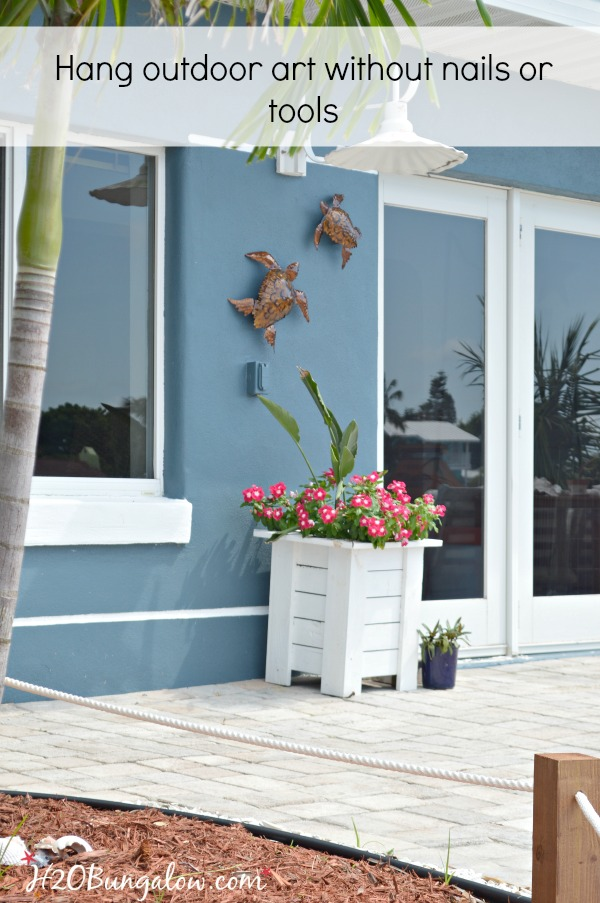 DIY tutorial to hang outdoor wall art without nails or tools on stucco,  siding or