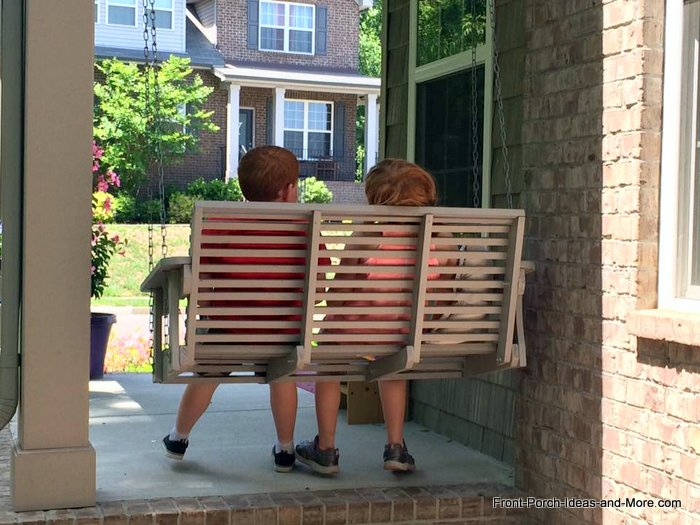 Children making memories on front porch swing